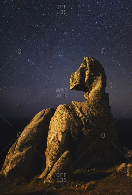 Starry night sky over small rock formation