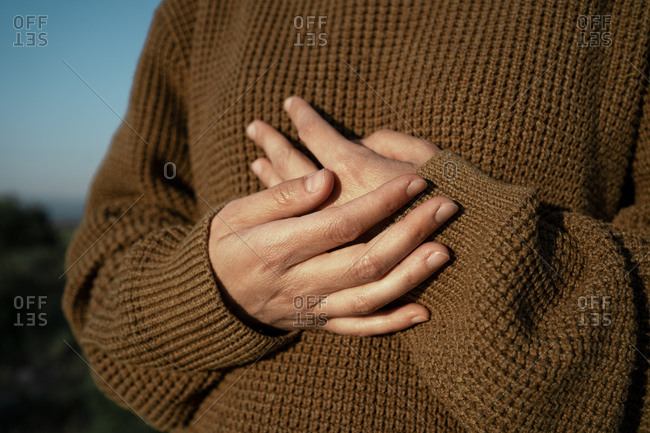 Hands of a woman wearing brown pullover