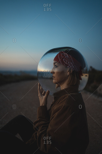 Woman with a fish bowl on her head sitting on a road in the countryside at dusk