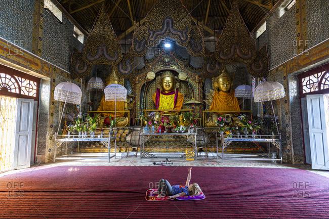 Myanmar- Shan state- Inn Thein- Girl lying on floor in Shwe Inn Dein pagoda