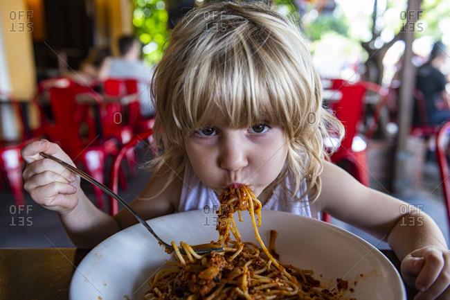Girl eating spaghetti at restaurant