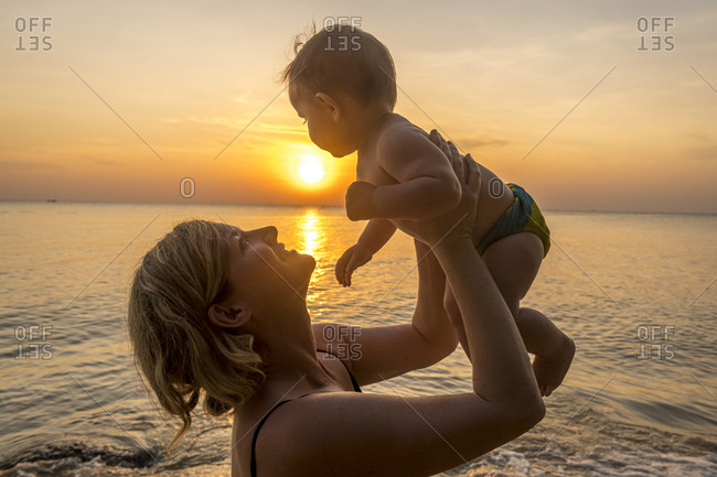 Vietnam- Phu Quoc island- Ong Lang beach- Mother holding baby in beach at sunset