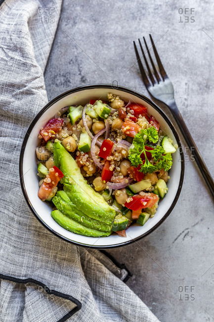 Bowl of vegetarian quinoa salad with chick-peas- avocado- cucumber- tomato- onion and parsley