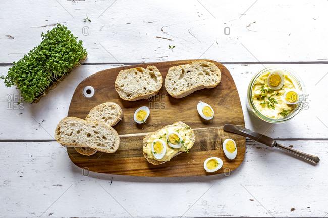 Sliced baguette and jar of homemade egg salad with cress