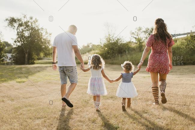 Family walking on a meadow in backlight