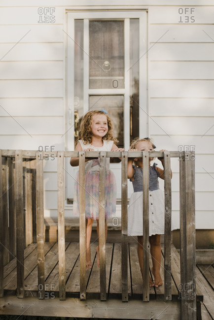 Two happy sisters standing on the porch at home