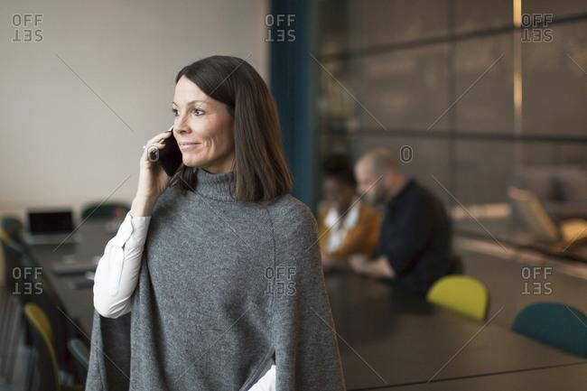 Businesswoman using phone in boardroom