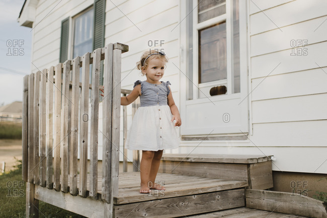 Cute girl standing on the porch at home