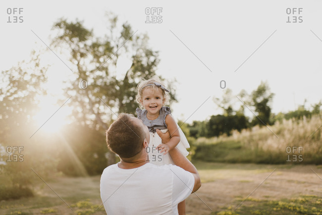 Father holding little daughter on a meadow in backlight