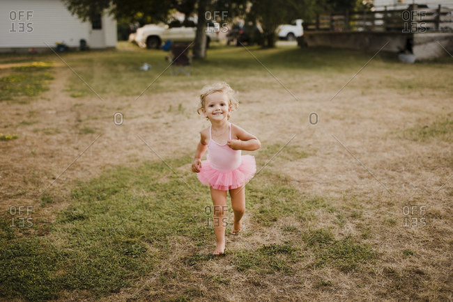 Happy little girl in a tutu running on a meadow