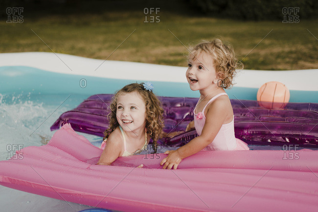 Two happy girls with airbed in an inflatable swimming pool