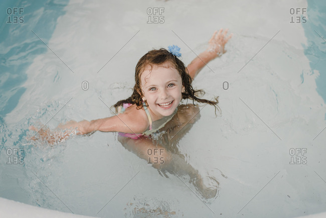 Portrait of a happy girl in an inflatable swimming pool