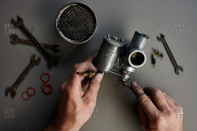 Top view of hand with vintage carburetor and tools in front of grey background
