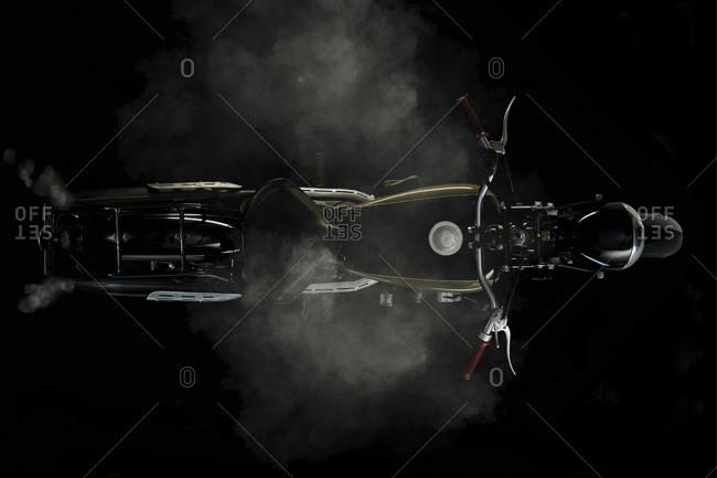 Top view of vintage motorcycle with smoke and black background (Ardie RZ 200 Peter)