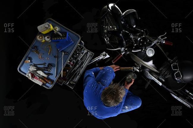 Top view of man repairing vintage motorcycle with black background (Ardie RZ)