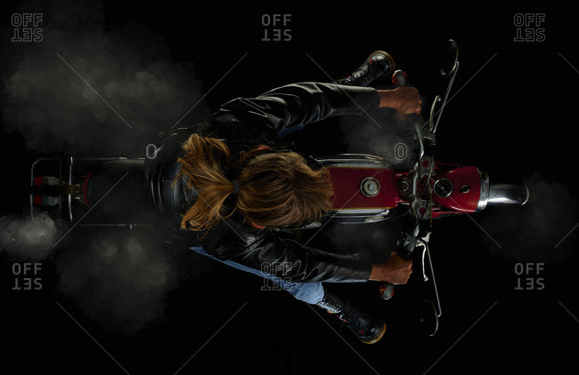 Top view of woman on vintage motorcycle with black background and smoke (Zuendapp KS 125 Sport)