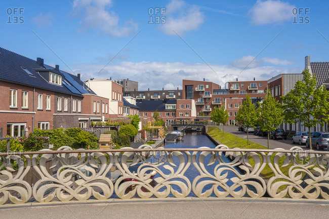 Netherlands- South Holland- Oegstgeest- Railing of bridge stretching over city canal with houses in background
