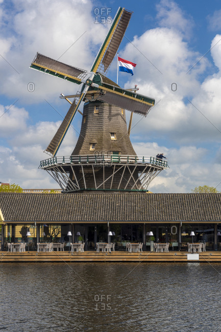 Netherlands- South Holland- Leiden- Riverbank restaurant in front of historic DHeesterboom windmill in background
