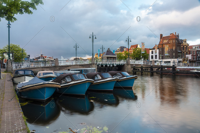 Netherlands- South Holland- Leiden- Motorboats moored in front of bridge in old harbor by Galgewater