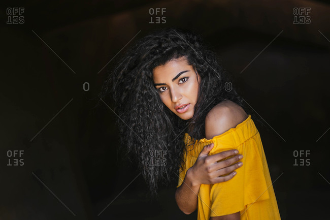 Portrait of young black-haired woman- dark background