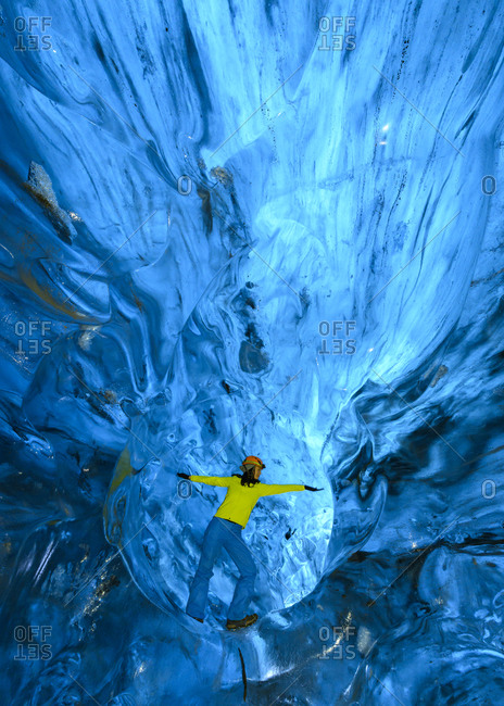Woman with arms outstretched in ice cave- Iceland