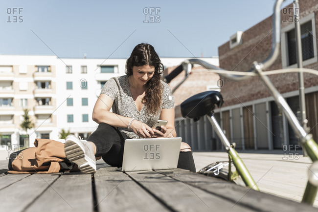 Young woman using smart phone while sitting with laptop on boardwalk in city