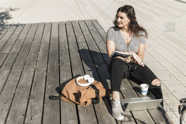 Thoughtful young woman looking away while sitting with laptop and backpack on boardwalk in city