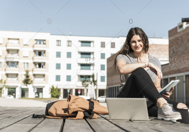 Smiling young woman with laptop and backpack sitting on boardwalk in city