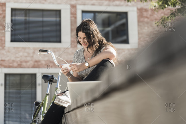 Smiling female student using mobile phone while sitting against building in city