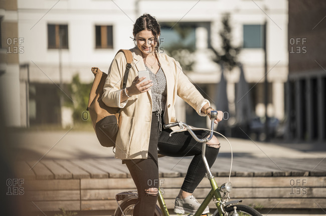 Female student using mobile phone while sitting on bicycle in city during sunny day