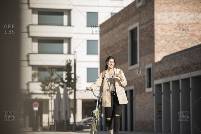 Female commuter using smart phone while walking with bicycle on city street