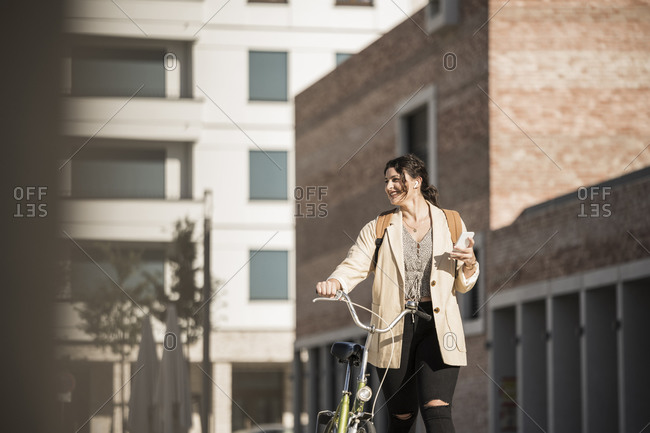 Smiling female student looking away while walking with bicycle against buildings