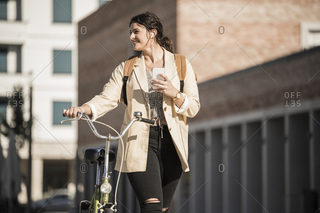 Smiling female student looking away while walking with bicycle against buildings in city