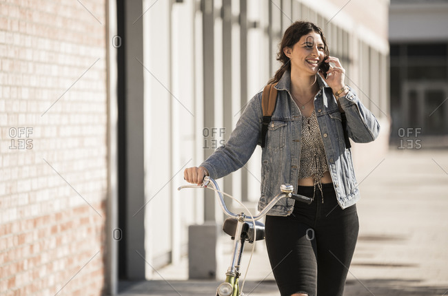 Smiling female student talking over mobile phone while walking with bicycle in city