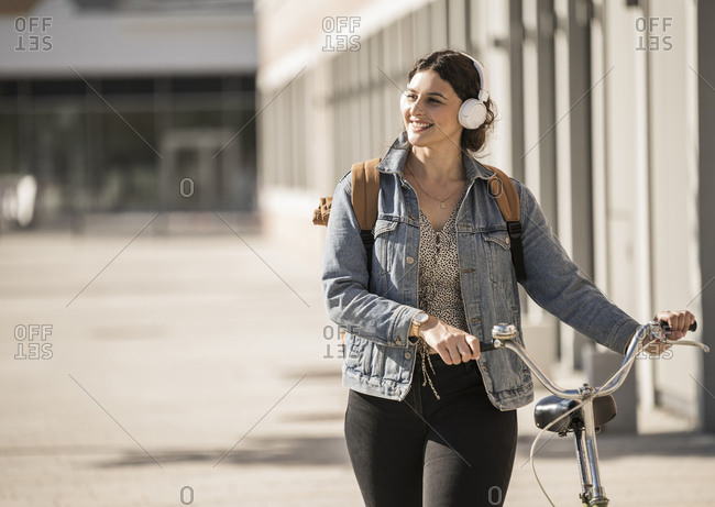 Smiling female commuter listening music while walking with bicycle on street in city