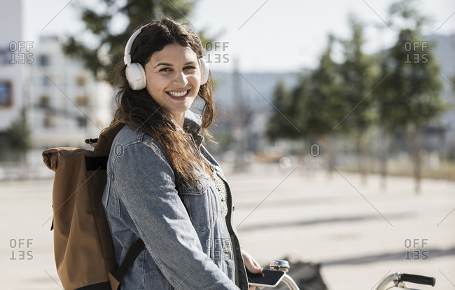Smiling female student listening music through headphones standing in city on sunny day