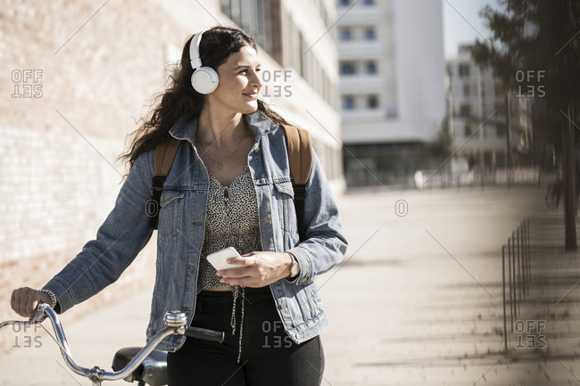 Young woman listening music looking away while standing with bicycle in city