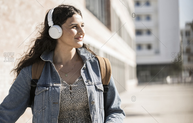 Young woman listening music through headphones looking away while standing in city