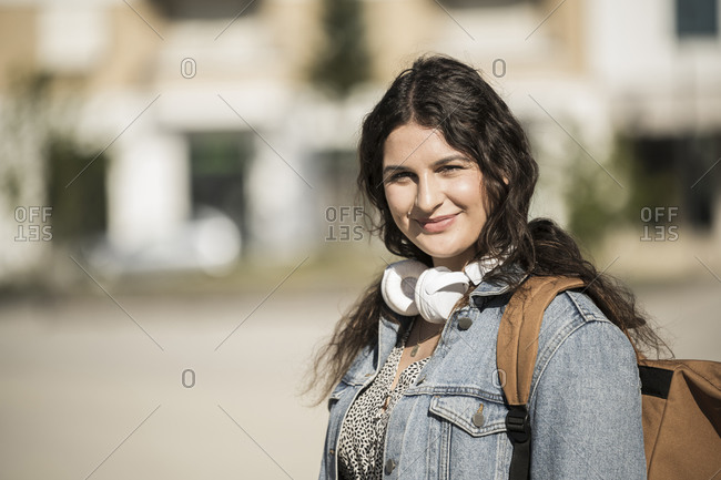 Smiling female student with backpack and headphones standing in city on sunny day