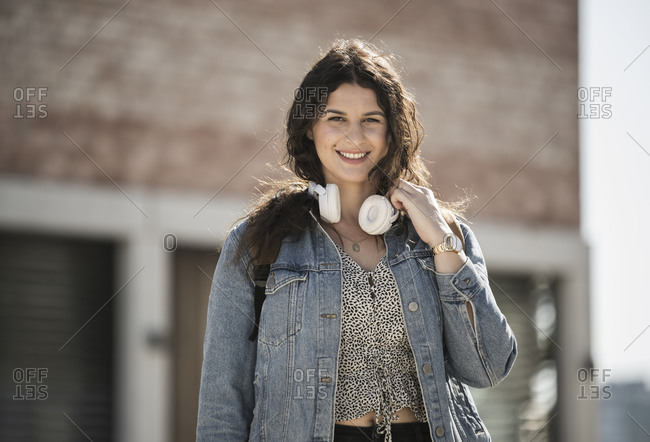 Smiling young woman with headphones standing in city on sunny day
