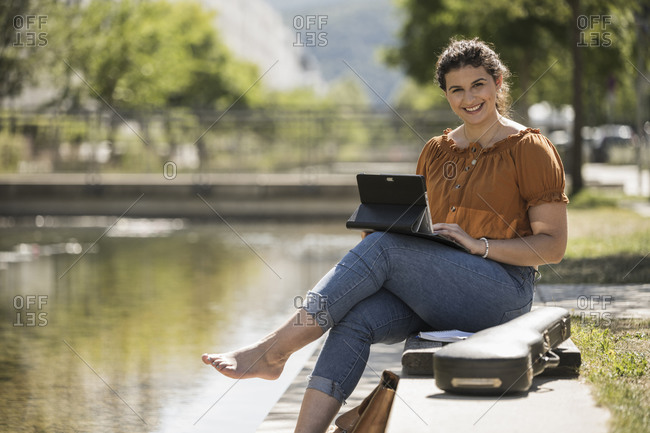 Smiling young woman using laptop while sitting by pond in park during sunny day