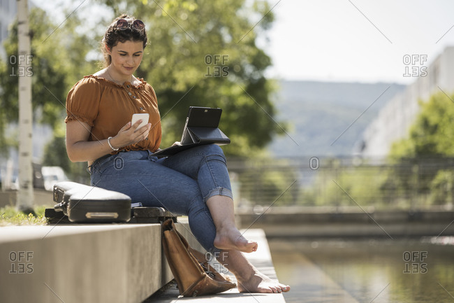 Woman with laptop using smart phone while sitting in park during sunny day
