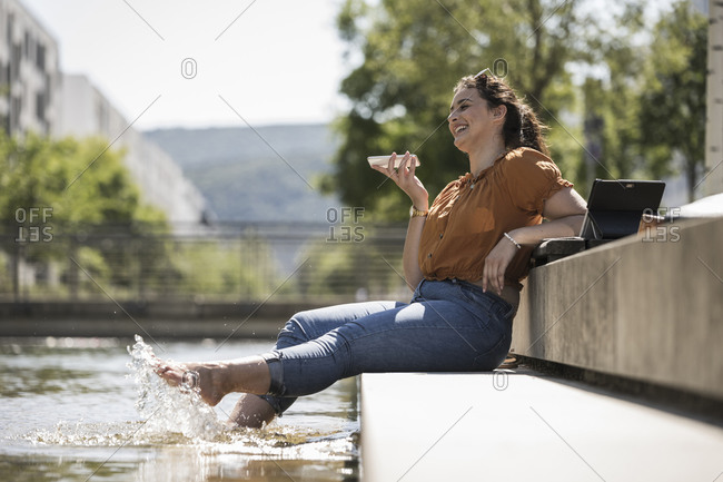 Cheerful woman with legs in pond talking over smart phone while sitting at park