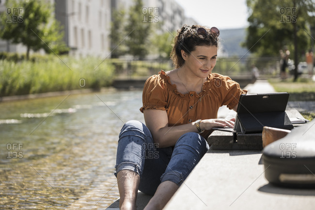 Woman using laptop while sitting by pond in park on sunny day