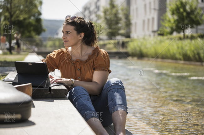 Thoughtful woman with laptop sitting by pond in park during sunny day