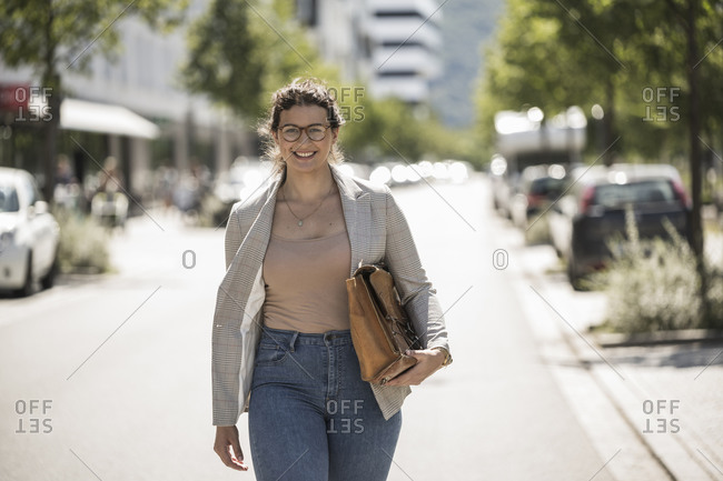 Smiling young woman carrying bag while walking on road during sunny day