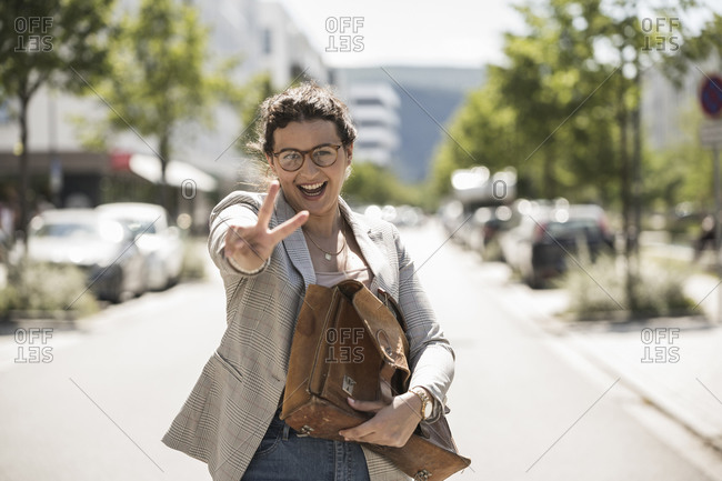 Cheerful young woman holding bag showing peace sign while standing on road in city