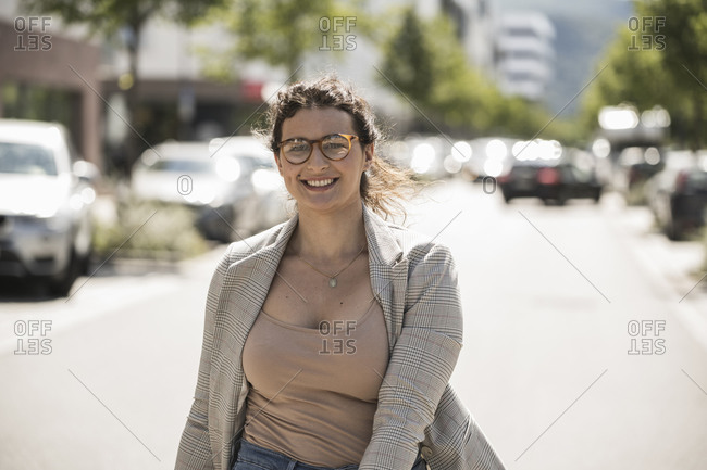 Smiling young woman wearing eyeglasses standing on street in city