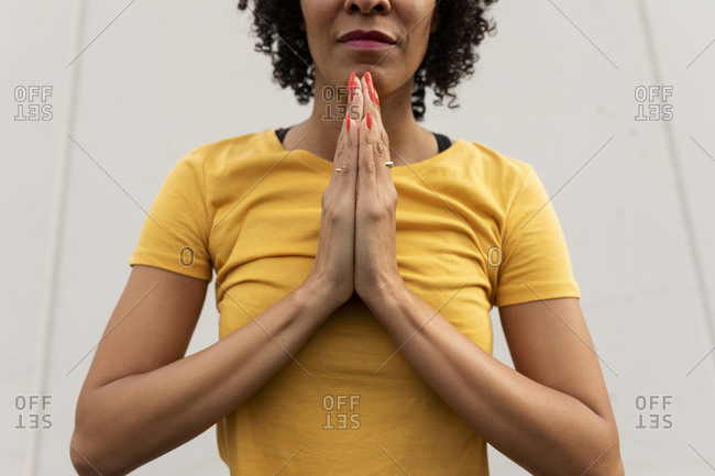 Close-up mid adult woman meditating while standing against wall in city