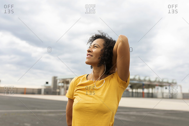 Smiling thoughtful woman looking up while standing against cloudy sky in city